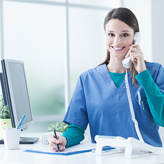 Medical professional on phone at reception desk