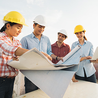 Individuals reading construction blueprints at a work site