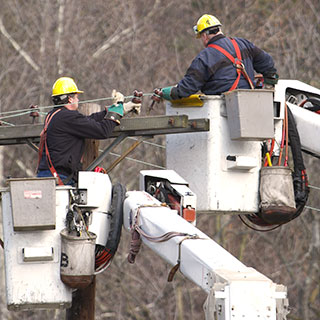 Utility workers in bucket trucks working on power lines