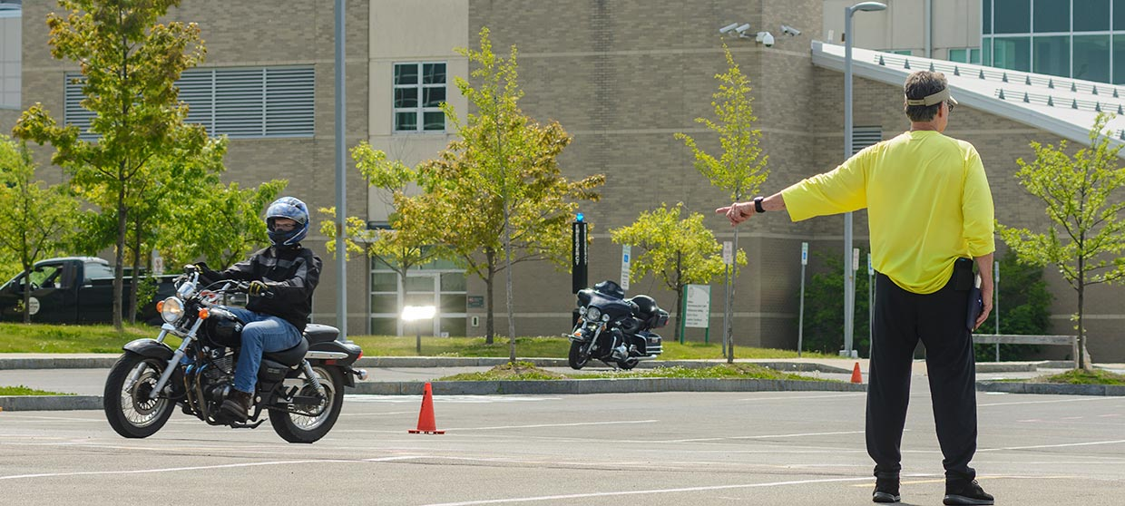Student riding a motorcycle in parking lot with instructor
