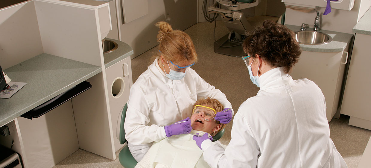 Dental assisting students working with dentist on patient