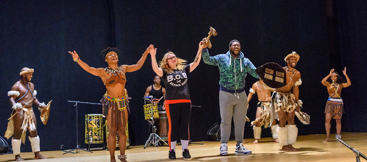 Students with performers from STEP AFRIKA on stage at an event on campus