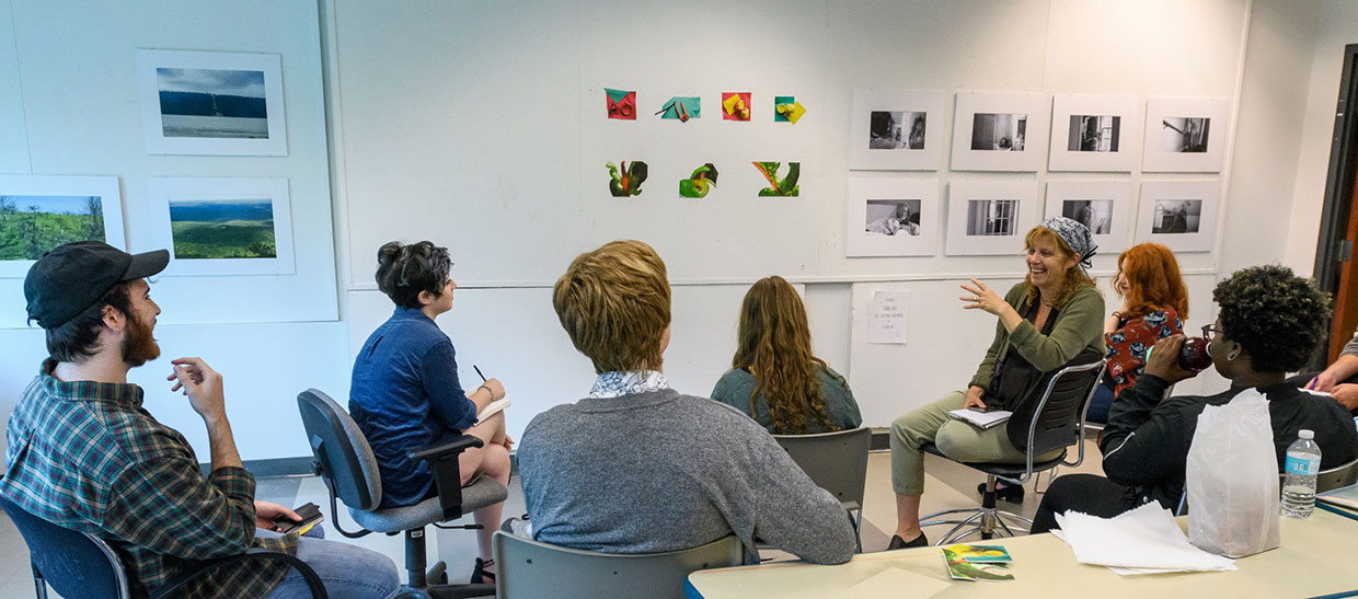 Students looking at artwork in a classroom with instructor