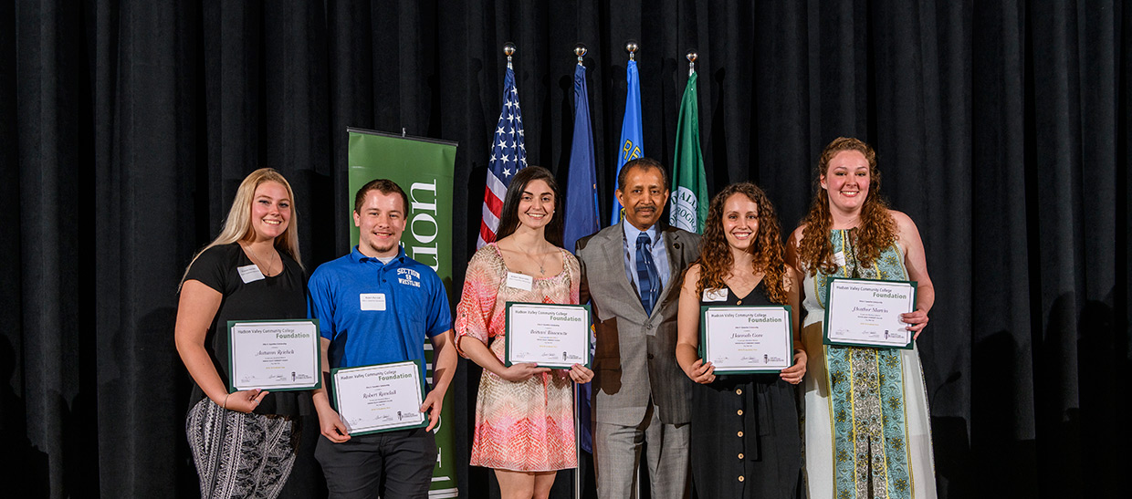 Students receiving scholarship from President Ramsammy