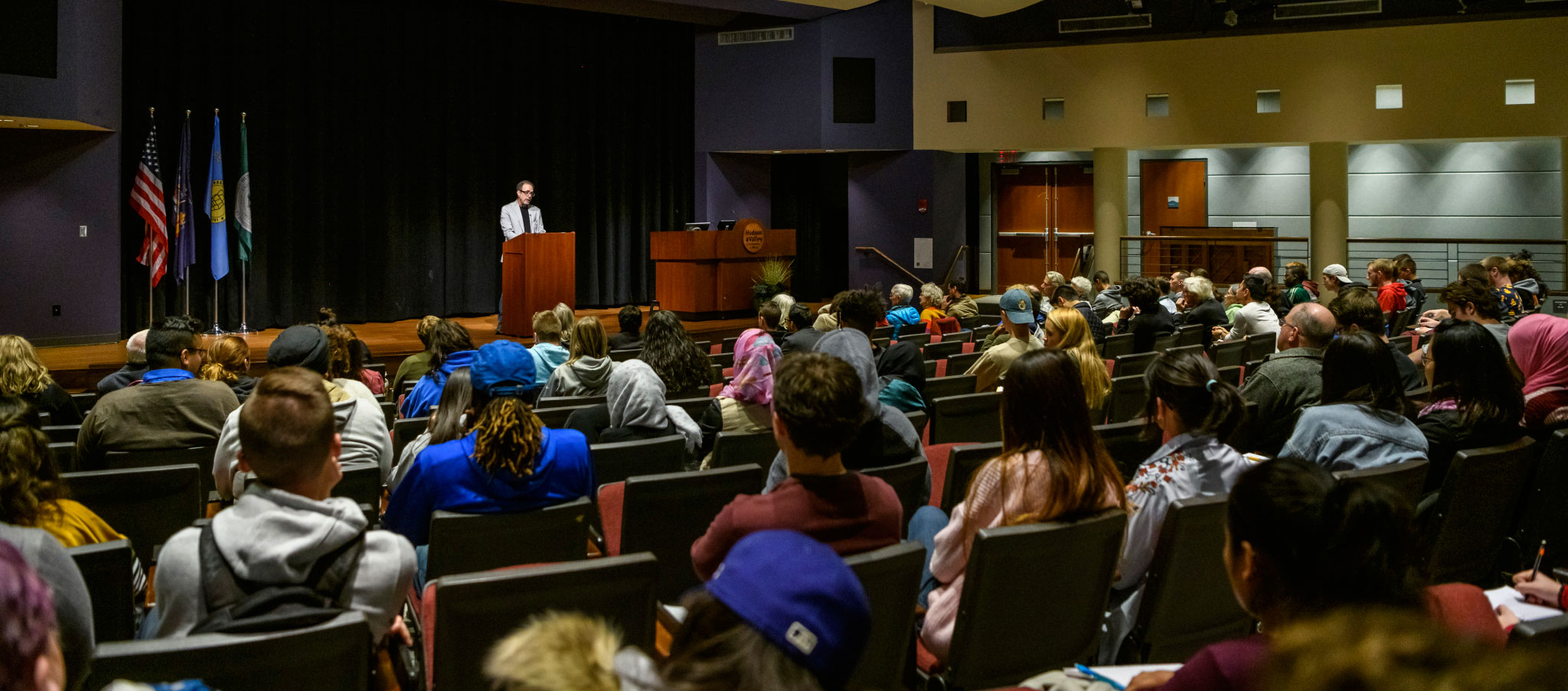 Students seated in the Bulmer Telecommunications Center Auditorium listening to a voices lecture