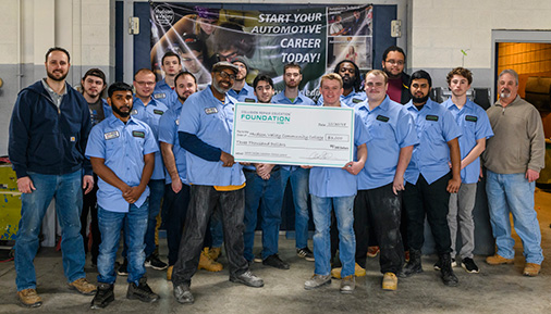 Autobody students and instructor pose with donation check
