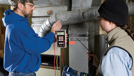 Two students testing the efficiency of a heating system