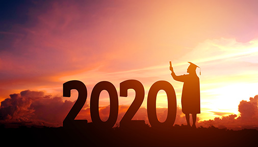 Silhouette of graduate next to a 2020 sign with sunset in background