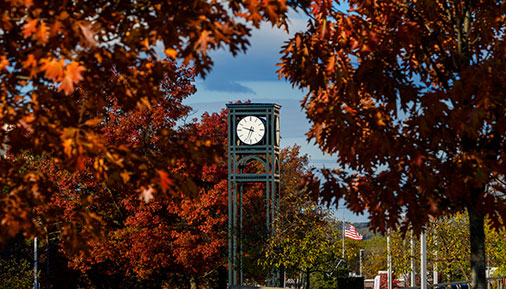 Clocktower on campus with fall leaves