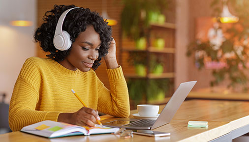 Smiling black girl with wireless headset studying online, using laptop at cafe, taking note